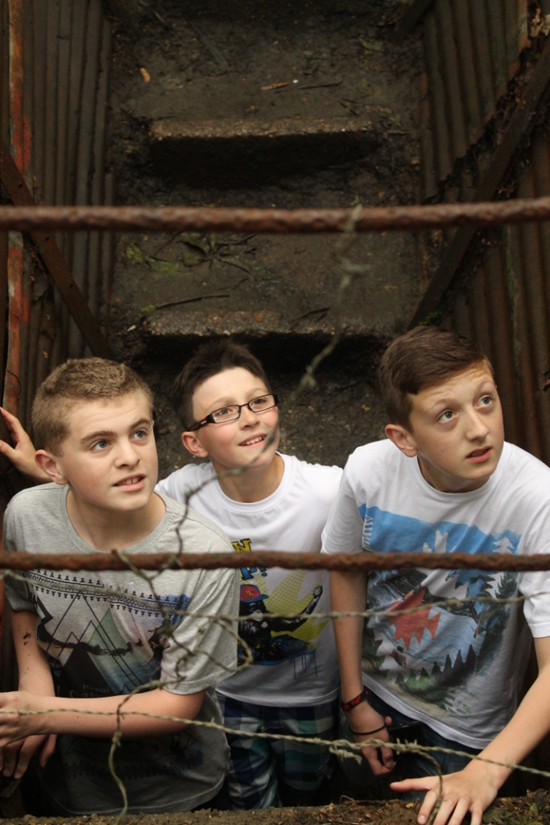 David, Adam and Thomas looking up from a trench