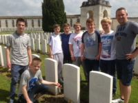 A cross with the school crest being laid at Tyne cot cemetery.